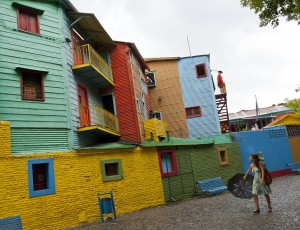 A stroller passes by brightly painted houses on 'Caminito' street.